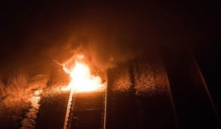 Demonstrators burn tire near freight-train tracks