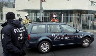Car daubed with anti-globalisation message crashes into gate of Angela Merkel's Berlin office